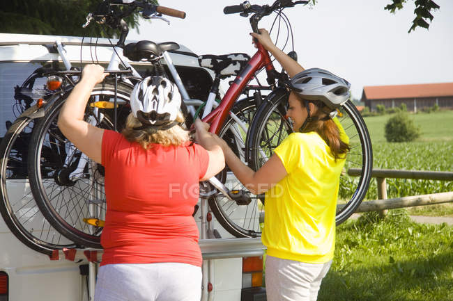 Two friends lifting bicycles from van outdoors — Stock Photo