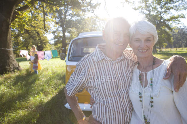 Senior couple arm in arm by camper van, smiling, portrait (lens flare) — Stock Photo