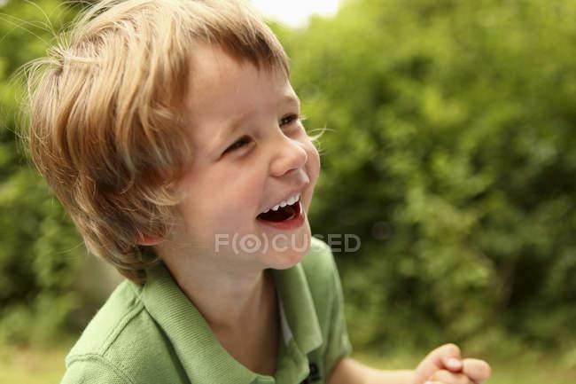 Фронтальний вид молодий хлопчик сміятися з defocussed фон — стокове фото