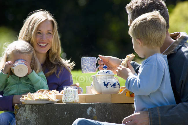 Happy family having outdoor lunch in countryside — Stock Photo