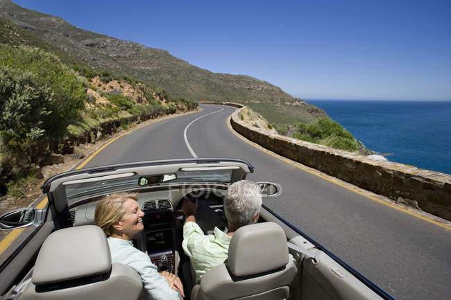 Couple driving convertible on coast highway — Stock Photo