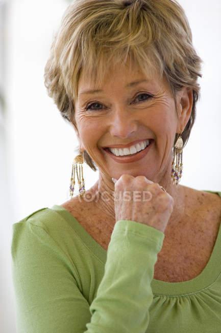 Ritratto della donna maggiore sorridente con sfondo sfuocato — Foto stock