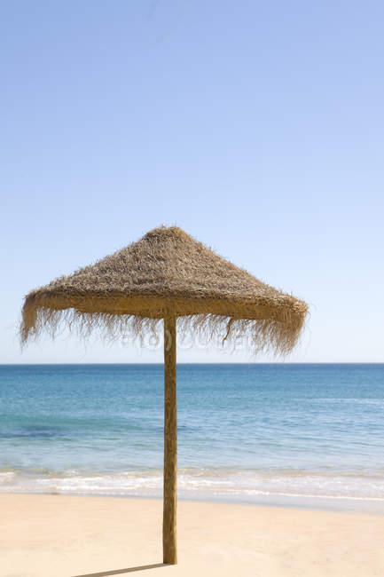 Крыша зонтик на тропическом пляже — стоковое фото