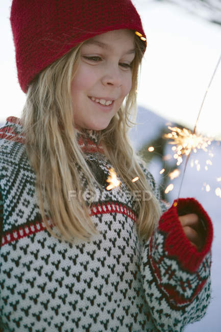 Girl holding sparkler with soft focus background — Stock Photo
