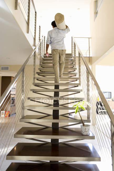 Низький кут зору людини, несучи прокату килим вгору сходами в новому будинку — стокове фото