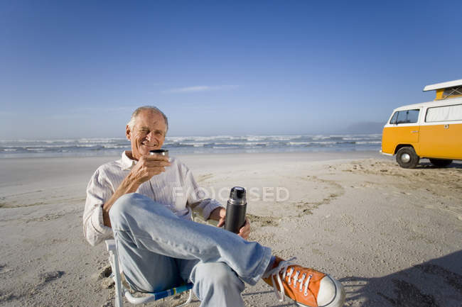 Senior man in chair on beach drinking from insulated flask, camper van in background, smiling, portrait — Stock Photo