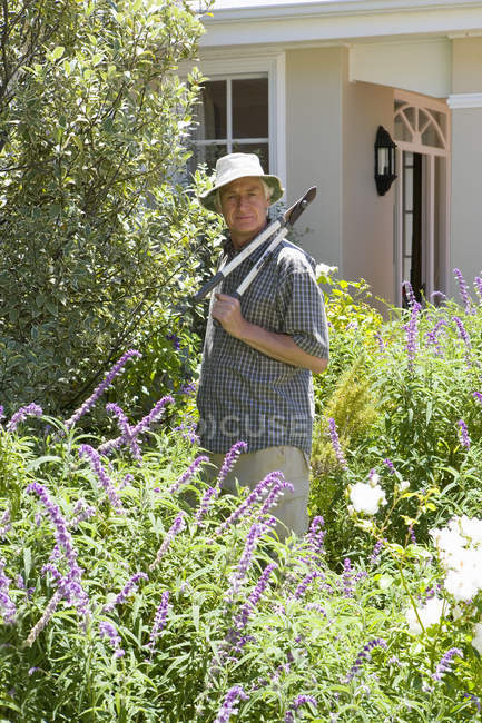 Front view of senior man in garden with shears — Stock Photo