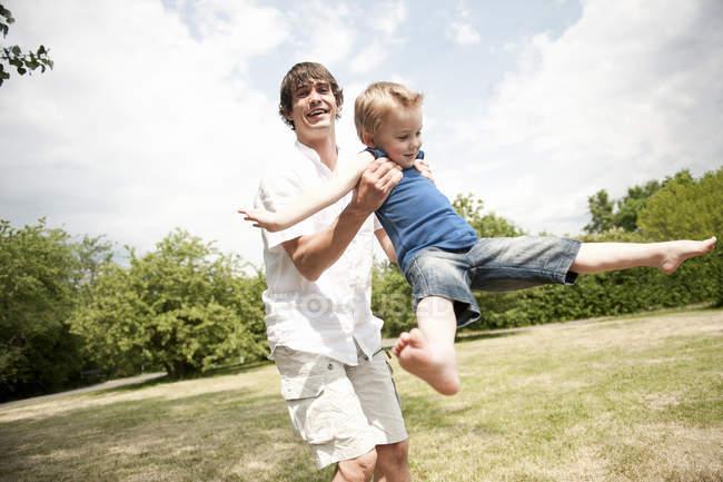 Vater Spinnerei Sohn um im park — Stockfoto