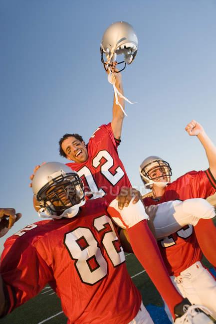 Американський футбол гравців в червоний футболу смужки святкувати перемогу після матчу — стокове фото