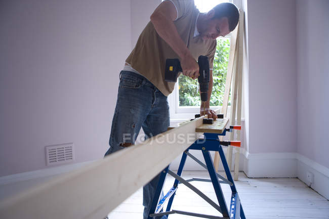 Man using electric drill on beam — Stock Photo