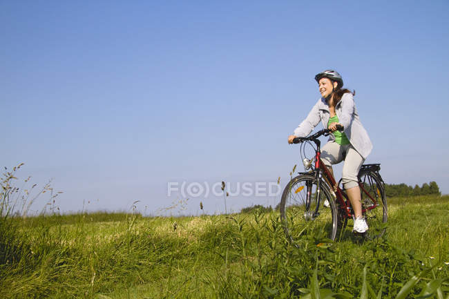 Young woman cycling through field — Stock Photo