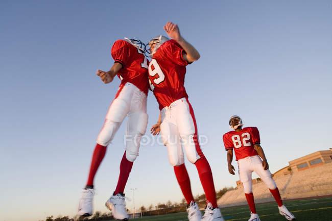 Два американских футболистов в красный футбольный полосы празднование приземления на поле на закате — стоковое фото