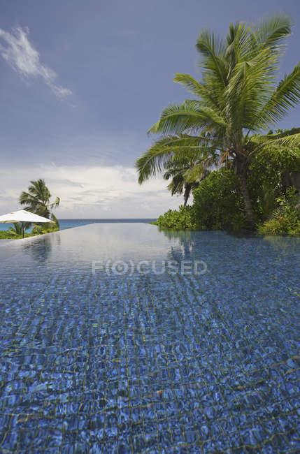 Piscina e palmeiras, Banyan Tree Hotel, Anse Intendance, Mahe ', Seychelles — Fotografia de Stock