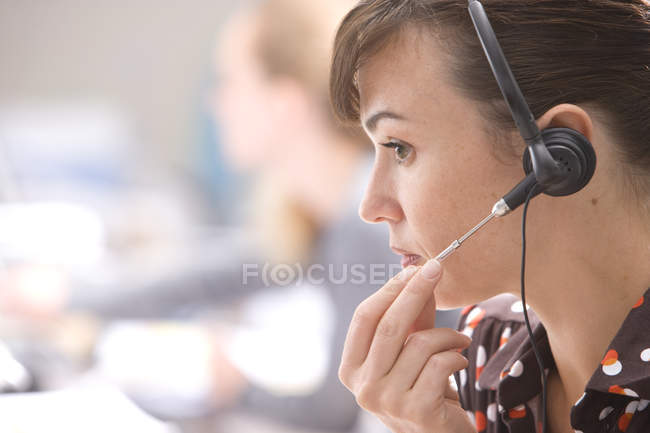 Vista lateral de la mujer con auriculares en call center - foto de stock