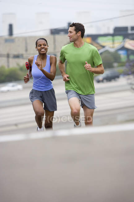 Front view of couple running outdoors - foto de stock