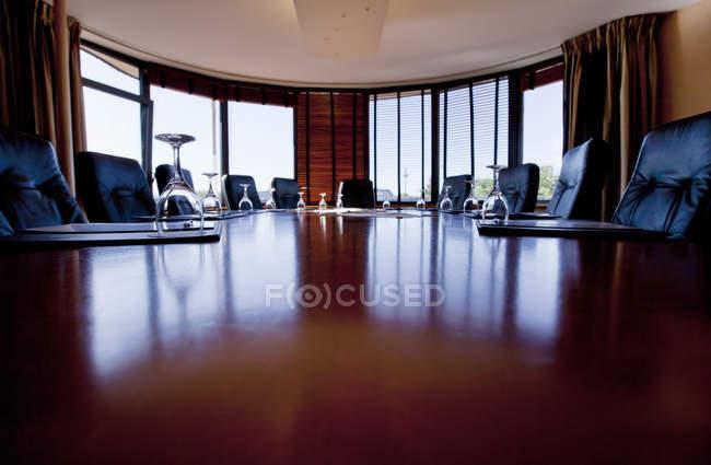 Поверхности уровня представления деревянных таблицы в Конференц-зал с стекла размещены вверх ногами — стоковое фото