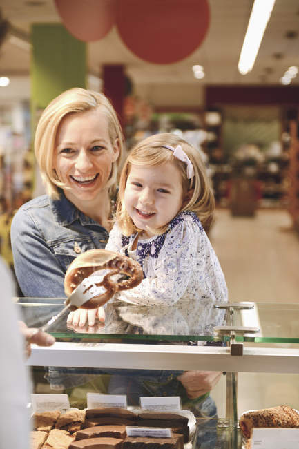 Mother and daughter shopping in an organic grocery store — Stock Photo