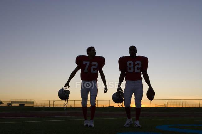 Два гравці американського футболу, залишаючи поле на заході сонця — стокове фото