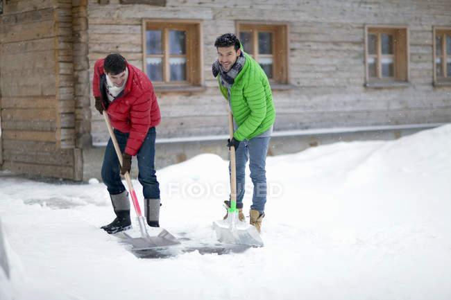 Men shoveling snow outside log cabin — Stock Photo