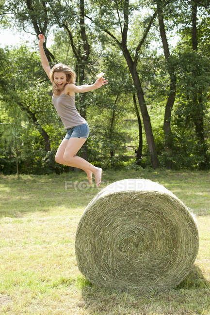 Young woman jumping from hay bale in field — side view, one