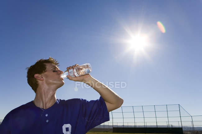 Low angle view of sportsman drinking water from bottle on pitch, lens flare — Stock Photo