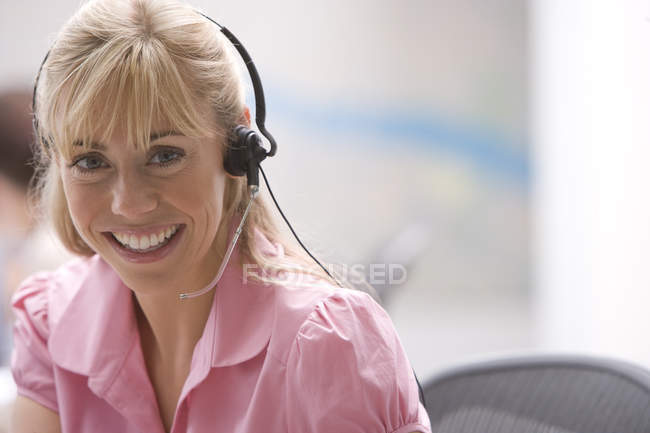 Vista frontal de la mujer con auriculares sonriendo en call center - foto de stock