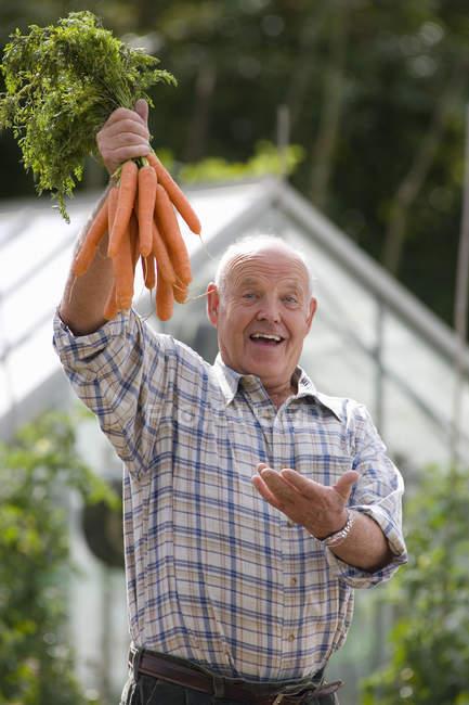 Senior man with carrots — Stock Photo