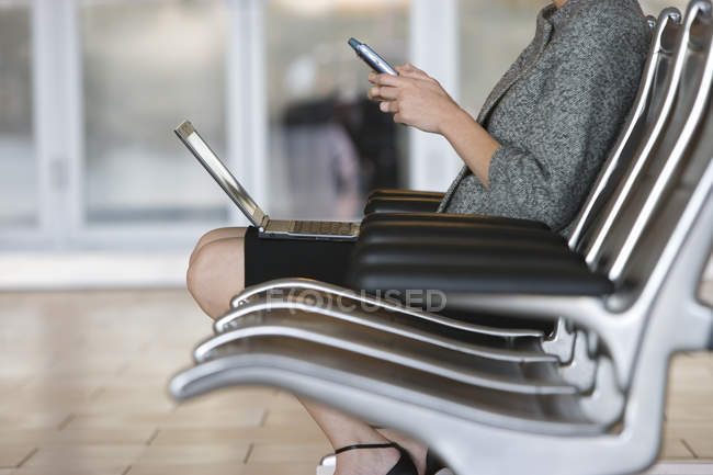 Crop image of woman using smartphone and laptop in airport waiting area — Stock Photo
