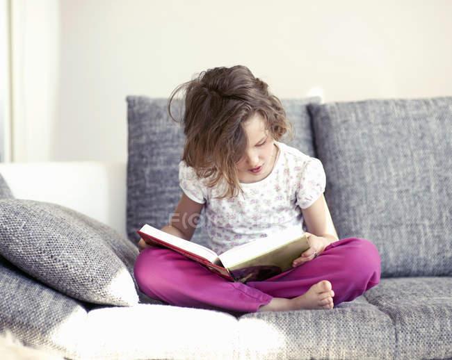 Garota sentada no sofá com as pernas cruzadas e lendo o livro — Fotografia de Stock