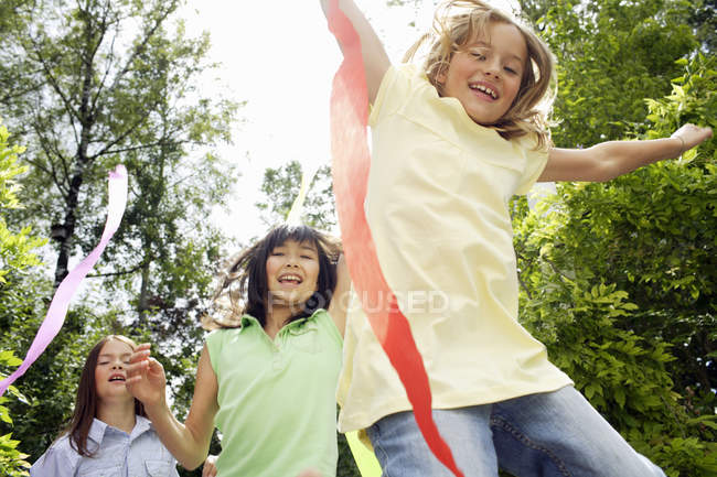 Young girls playing outdoors with streamers — Stockfoto