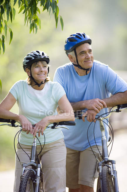 Mature couple cycling outdoors and smiling — Stock Photo