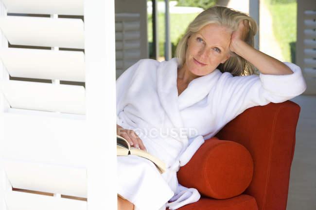 Woman sitting on sofa wearing white bathrobe — Stock Photo