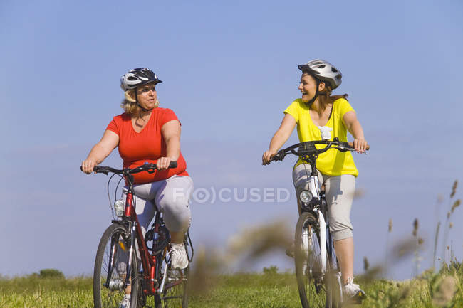 Two friends riding bicycles through field — Stock Photo