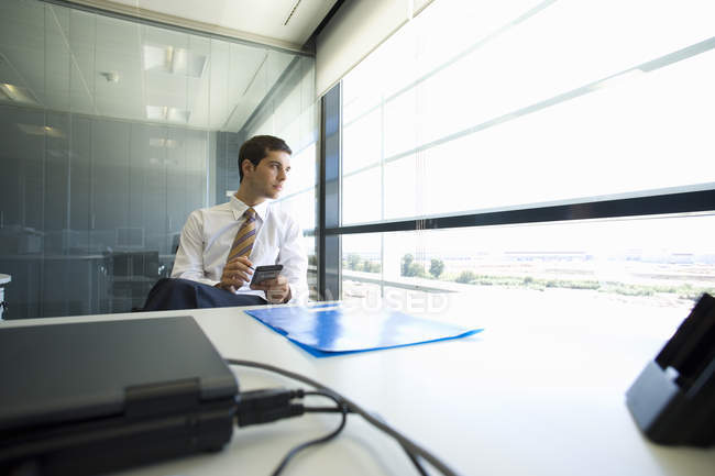Businessman using electronic organizer in office — Stock Photo
