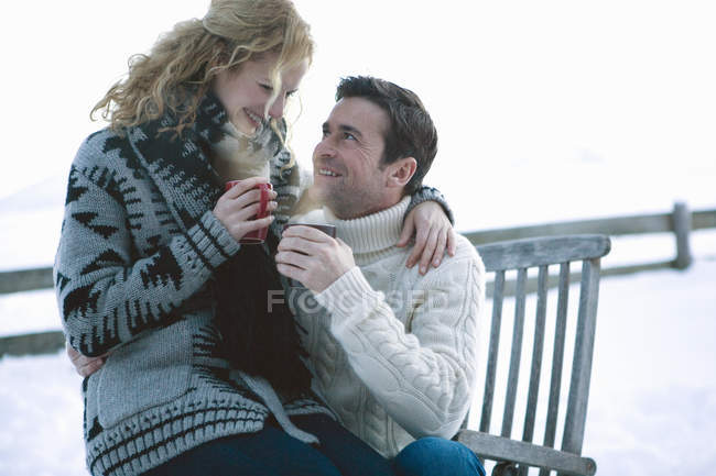 Woman sitting on knees of man, couple holding hot drinks in winter — Stock Photo