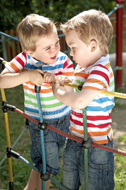 Брати-близнюки сходження на тросах в дитячий майданчик — стокове фото