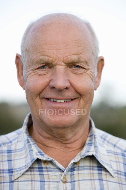 Portrait of senior man in checked shirt on blurred background — Stock Photo