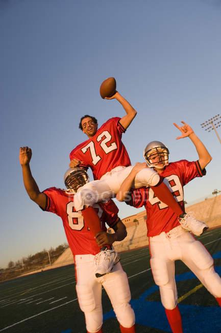 Американский футбол игроки в красный футбольный полоски празднует победу пост матч — стоковое фото