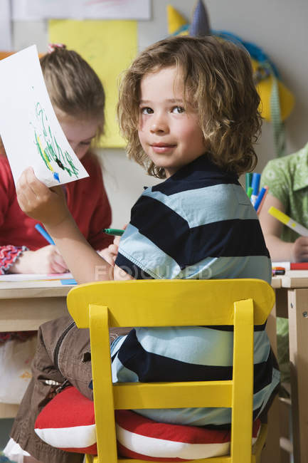 Preschool boy holding colored picture at desk — Stock Photo