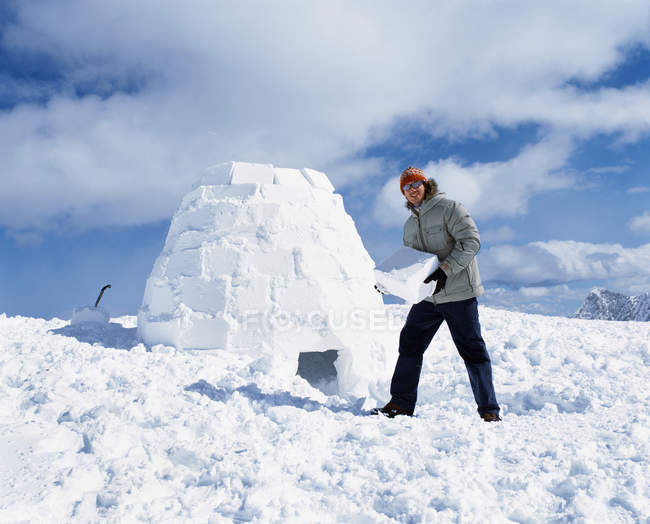 Man holding ice block and building igloo — leisure activity