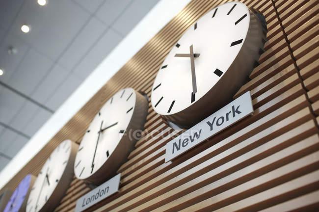 Vista de ángulo bajo de las zonas horarias mundo relojes en fila en la pared de madera - foto de stock