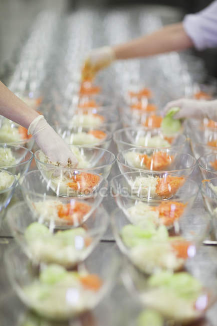 Assembly line of salad bowls with soft focus background — Stock Photo