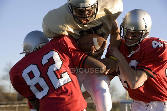Jugador de fútbol americano decidido correr con la bola durante el juego - foto de stock