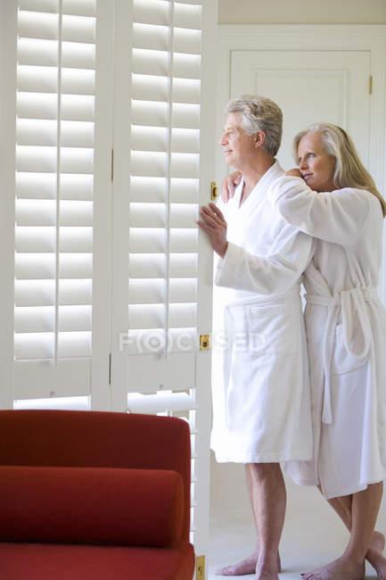 Літня пара стоячи за вікном — стокове фото