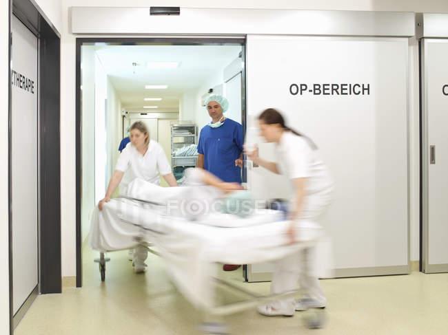 Movimiento borrosa de médico y enfermeras teniendo la paciente en quirófano en el hospital - foto de stock