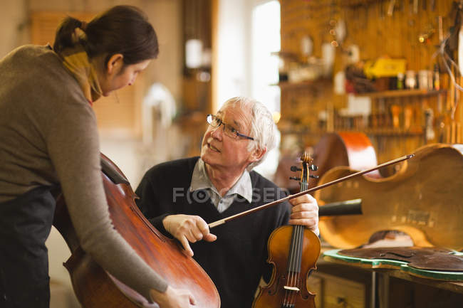 Luthiers, discutant des instruments dans l'atelier — Photo de stock