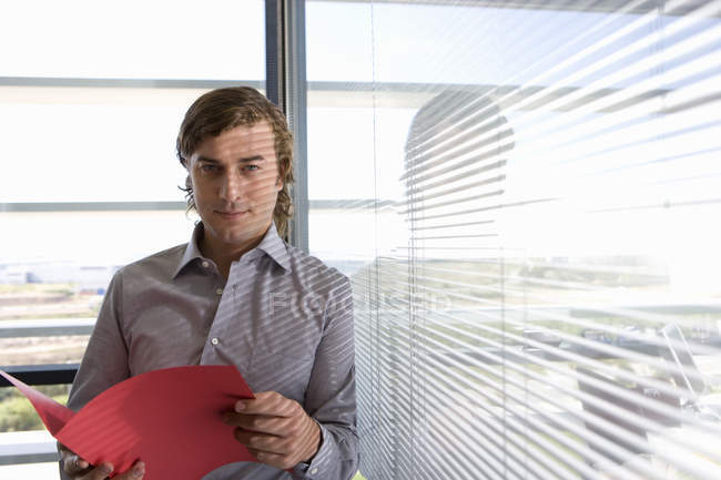 Businessman with file by window and looking at camera — Stock Photo