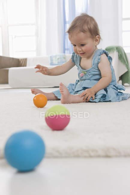 Молодий хлопчик, сидячи на підлогу грав деякі кольоровими кулями — стокове фото