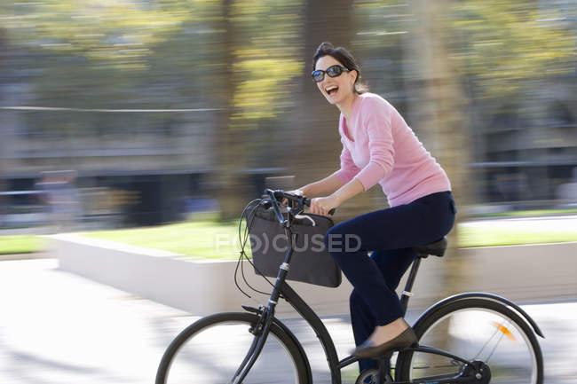 Vista laterale della bicicletta di guida della donna con sfondo sfuocato — Foto stock