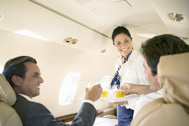 Smiling stewardess serving tray with glasses of orange juice to entrepreneurs in private airplane — Stock Photo